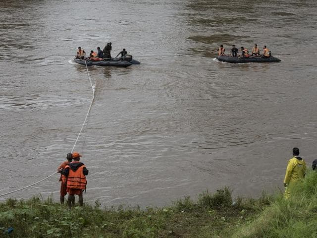 Divers from the NDRF, Indian Navy and Indian Coast Guard look for wreckage of vehicles swept away in the Savitri river after the Mahad bridged collapsed.