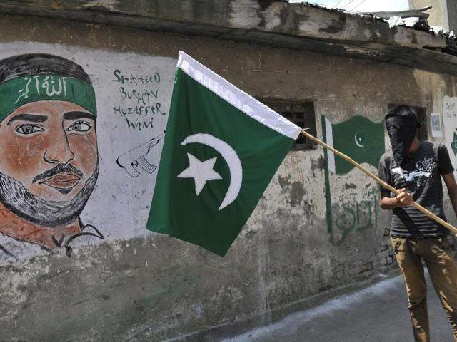 A masked Kashmiri protester holds a Pakistan flag next to a graffiti of Hizbul Mujahideen commander Burhan Muzaffar Wani in Srinagar.(Waseem Andrabi/ HT Photo)