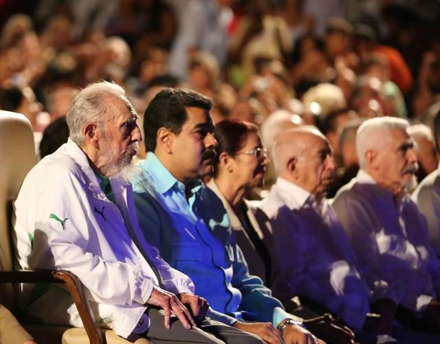 In this handout picture released by Prensa Miraflores, former Cuban President Fidel Castro (L), sitting next to Venezuelan President Nicolas Maduro (2nd L), is seen attending the celebration of his 90th birthday at the Karl Marx theatre in Havana on August 13, 2016.