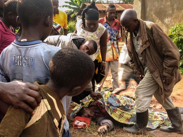 Residents of the village of Oicha-Tenabo, 36 km from the city of Beni, look at the dead body of a victim of attacks in eastern Congo's North Kivu province where nine civilians were murdered on July 5, 2016.