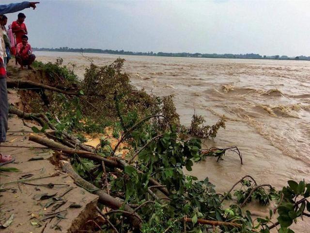 Villagers watch land erosion along a river at a flood-hit village in Kishanganj district of Bihar.