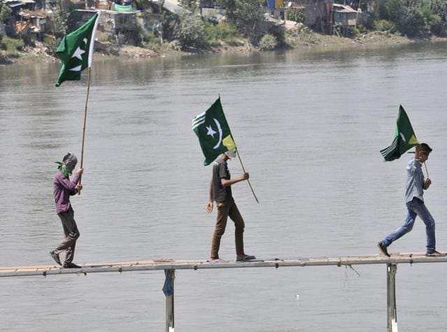 Kashmiri protesters hold Pakistani flags in Srinagar on Sunday.