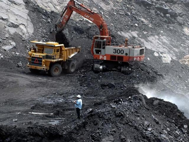 Workers use heavy machinery to shift a pile of coal at an open cast mine owned by The Sinagareni Collieries Company Limited (SCCL) at Godavarikhani, some 250 kilometers east of Hyderabad.