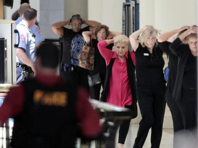 Mall workers and visitors exit to safety through the upper floor food court at Crabtree Valley Mall with hands on their heads as the mall is evacuated in Raleigh, NC.