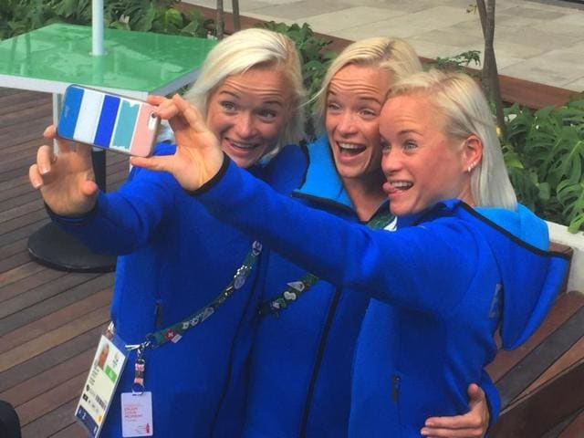 Estonian triplets, from left, Leila, Liina and Lily Luik take a selfie outside the Main Press Center at the 2016 Summer Olympics in Rio de Janeiro, Brazil.
