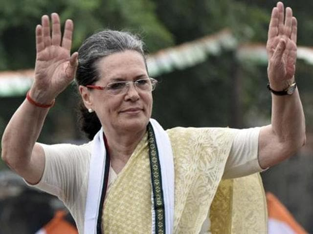 Congress president Sonia Gandhi waves towards supporters during a roadshow in Varanasi.