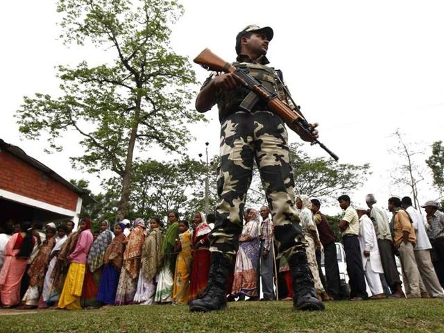 A securityman stands as people line up to cast their vote outside a polling station in Nakhrai village in Tinsukia.