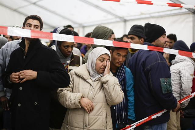 Migrants wait for transport to a registration office at the State Office of Health and Welfare in Berlin.