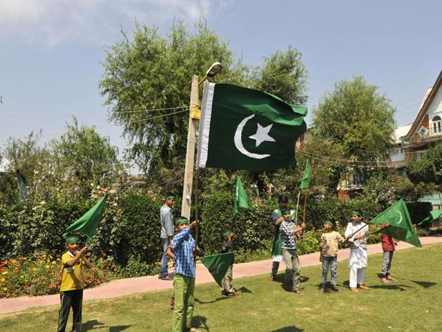A boy hold a flag of Pakistan during celebrations marking Pakistani Independence Day in Srinagar