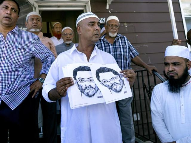 Members of the the Al-Furqan Jame Masjid mosque  display a police sketch of a suspect believed to have shot the mosque's imam.