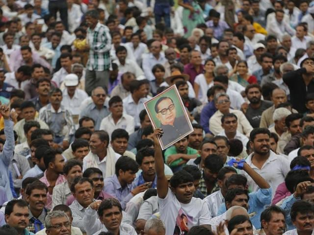 A man displays a portrait of Dalit leader BR Ambedkar as hundreds of members of the Dalit community gather for a rally in Una.(AP)