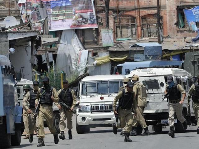 Policemen take position outside a building where militants were believed to be holed up in downtown Srinagar.