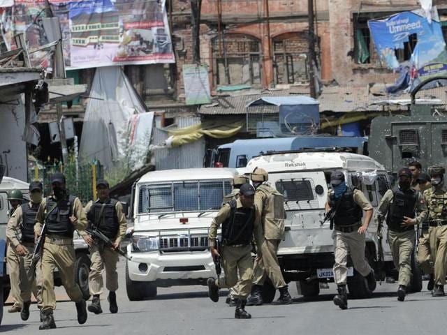 Police run from the building where an encounter was underway in Srinagar.
