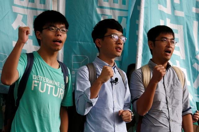 Wong, Law and Chow chant slogans before the verdict, on charges of inciting and participating in an illegal assembly in 2014 which led to the pro-democracy movement.