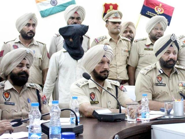 Police with the accused (face covered) at a press conference over the Quran desecration incident in Sangrur on Tuesday.