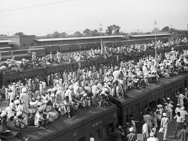 """A train crammed with refugees leaves for Pakistan from the border city of Amritsar in 1947. Although these trains traveled on confidential routes with armed guards, they were still attacked. After one such attack, photojournalist Margaret Bourke-White arrived at the Amritsar station to find men from the """"militant Akhali sect..sitting cross-legged"""" on the platform, sword in hand, """"patiently waiting for the next train."""""""