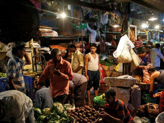 Vendors work at a wholesale vegetable market in Mumbai on Tuesday