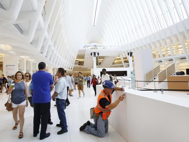 A worker makes finishing touches in the World Trade Center Transportation Hub, in New York. The Westfield World Trade Center, a retail mall, opened in the hub on Tuesday.