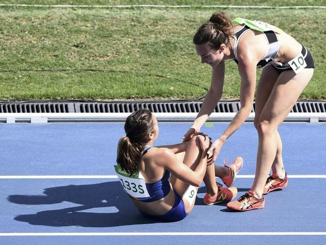 Nikki Hamblin (left ) of New Zealand helps fellow competitor Abbey D'Agostino of USA during the 5000m heats in Rio on Tuesday.