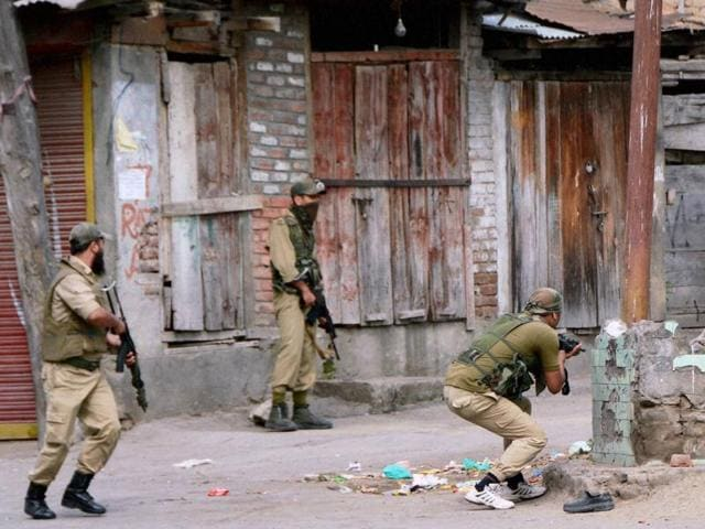 Special Operation Group (SoG) of Jammu and Kashmir Police personnel take positions during an encounter with the militants at Nowhatta in Srinagar on Monday. Militants staged another attack on Wednesday morning.