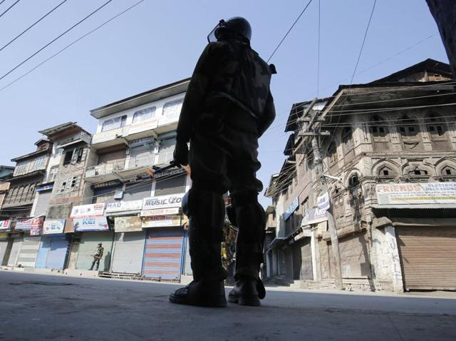 A paramilitary soldier stands guard on a street with closed shops and stores in the Maisuma area of Srinagar.