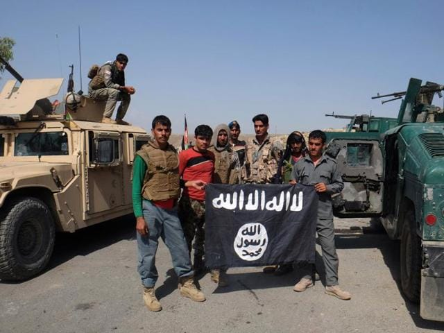 Afghan police pose for a photograph with an Islamic State flag after an operation in the Kot district of Jalalabad province east of Kabul.