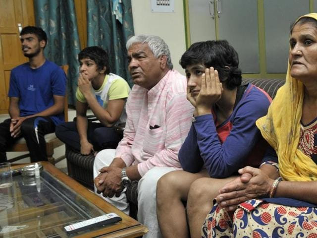 Coach Mahavir Phogat watches Vinesh's Olympic bout at their home in Balali  village in in Bhiwani district on Wednesday.