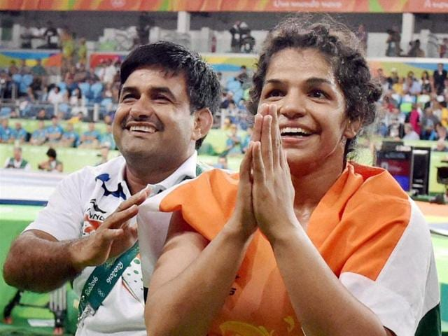 India's Sakshi Malik, with her coach Kuldeep Singh, celebrates after winning bronze against Kyrgyzstan's Aisuluu Tynybekova in the women's wrestling freestyle 58-kg competition