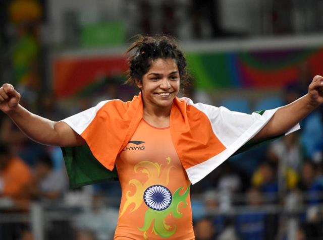A triumphant Sakshi Malik drapes the Indian flag on her shoulders after winning bronze in the women's wrestling freestyle 58kg event at the Rio Olympics.