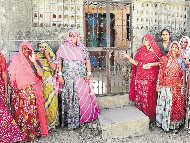 Women in Kachhabali stand outside the liquor shop that was shut down after a voting was held over the issue.