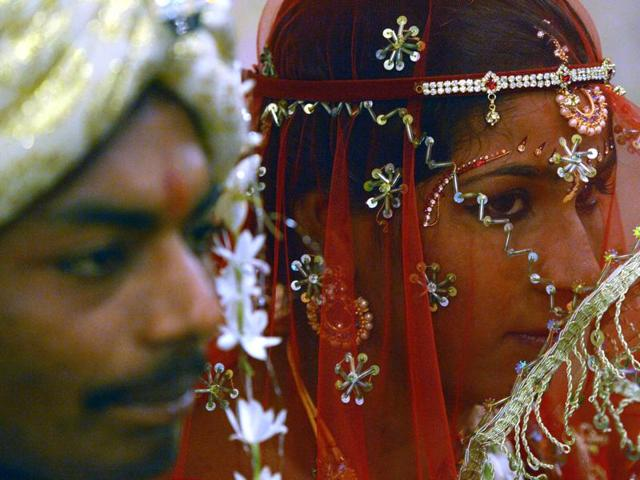 A Pakistani Hindu bride (R) and a groom attend a mass wedding ceremony in Karachi on January 24, 2016.