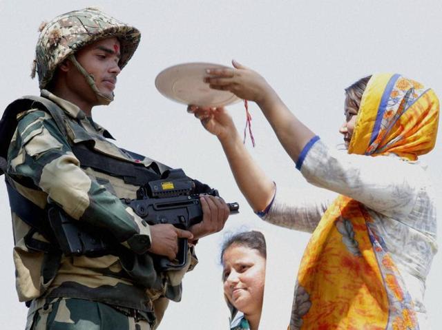 On the occasion of Raksha Bandhan, a girl ties Rakhi on a BSF jawan's wrist near International Border in Jammu. (PTI)