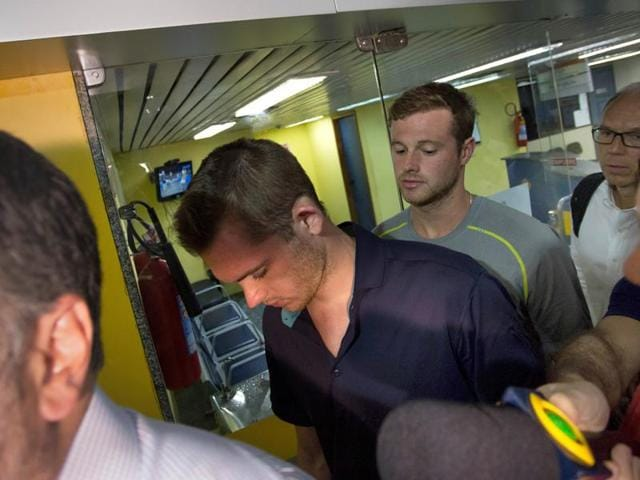 Journalists surround American Olympic swimmers Gunnar Bentz, left, and Jack Conger, centre, as they leave the police station at Rio International airport. The two were taken off their flight from Brazil to the US on Wednesday by local authorities amid an investigation into a reported robbery targeting Ryan Lochte and his teammates.
