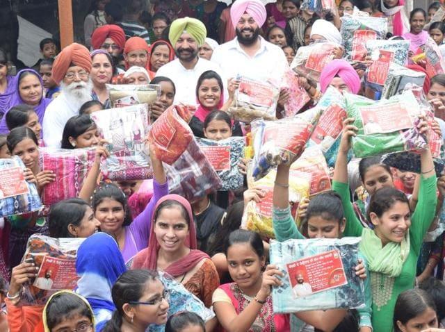 SAS Nagar MLA Balbir Singh Sidhu distributing suits to unmarried women at Balongi in SAS Nagar on Raksha Bandhan.