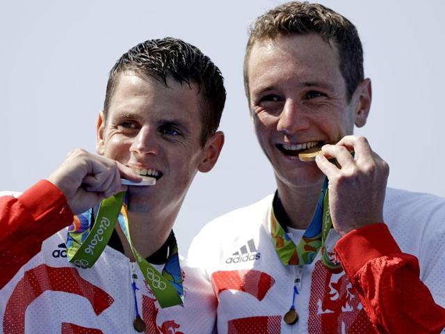 Gold medallist Alistair Brownlee and silver medallist Jonathan Brownlee lie on the ground after the triathlon race.