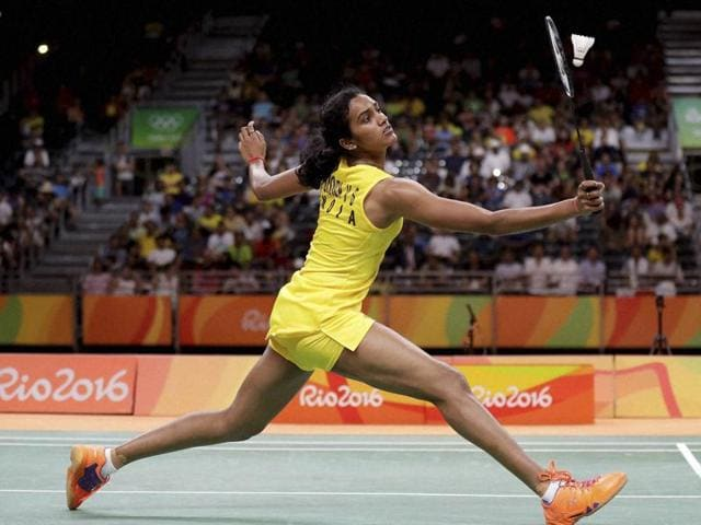 PV Sindhu of India clasps hands with Nozomi of Japan over the net after winning their match.