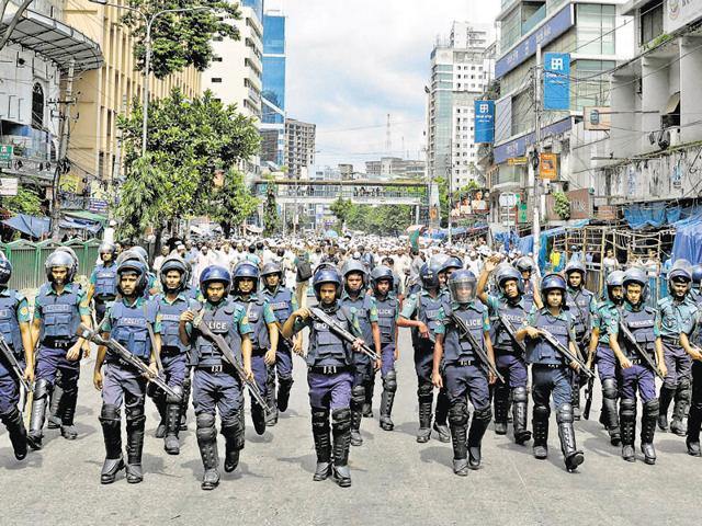 File photo of Bangladeshi police standing guard in front the house where police killed nine suspected Islamist extremists in Dhaka on July 26.