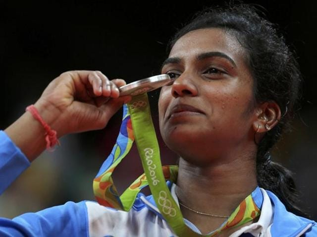 Silver medallist P.V. Sindhu (IND) of India poses with an Indian national flag.