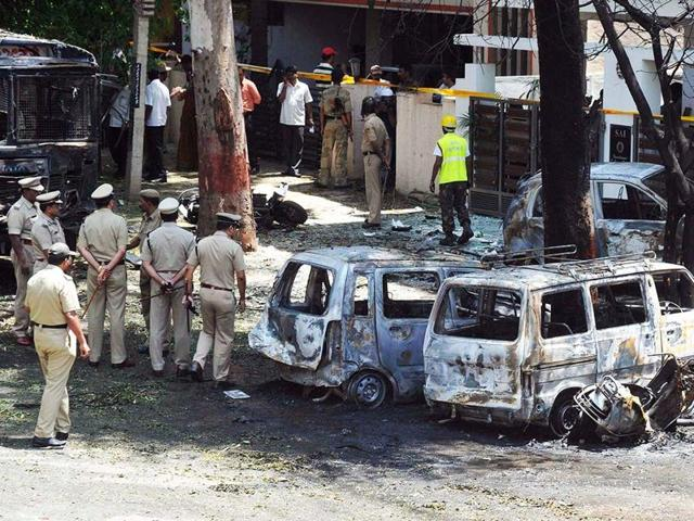 Policemen walk past damaged vehicles at the scene of a blast near BJP's office in Bengaluru.