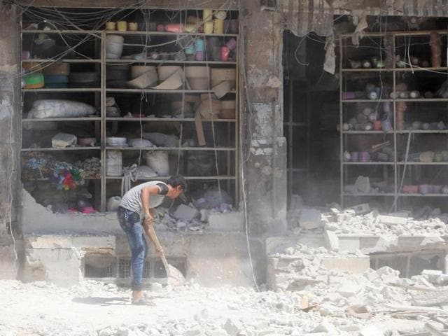 A man removes the rubble in front of a damaged shop after an airstrike in the rebel held al-Saleheen neighbourhood of Aleppo, Syria.