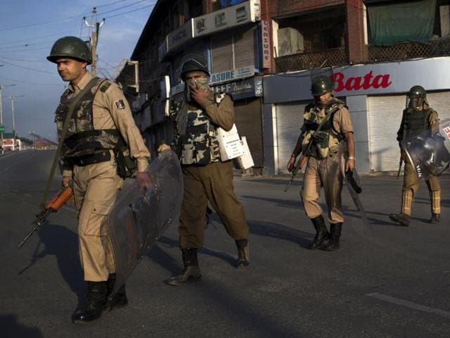 Paramilitary soldiers patrol during curfew in Srinagar.
