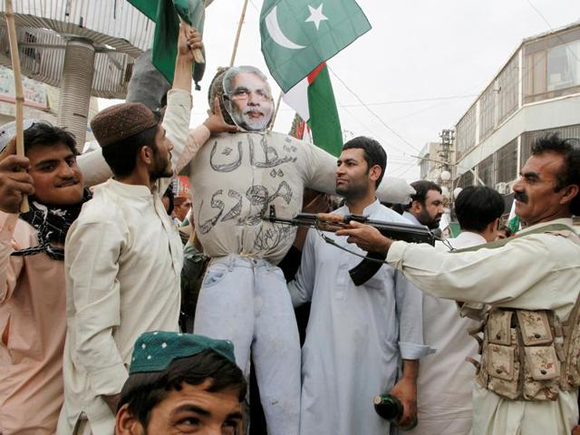 A man points his weapon at an effigy depicting India's Prime Minister Narendra Modi, while chanting slogans during an anti-India protest in Quetta on Thursday.