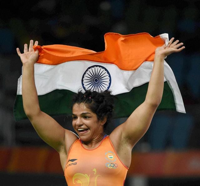 Sakshi Malik along with her coach Kuldeep Singh celebrates after winning bronze medal of the women's wrestling freestyle 58-kg competition.
