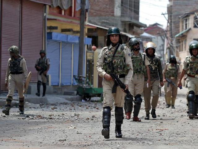 Security force personnel patrol a street in Srinagar as the city remains under curfew following weeks of violence.