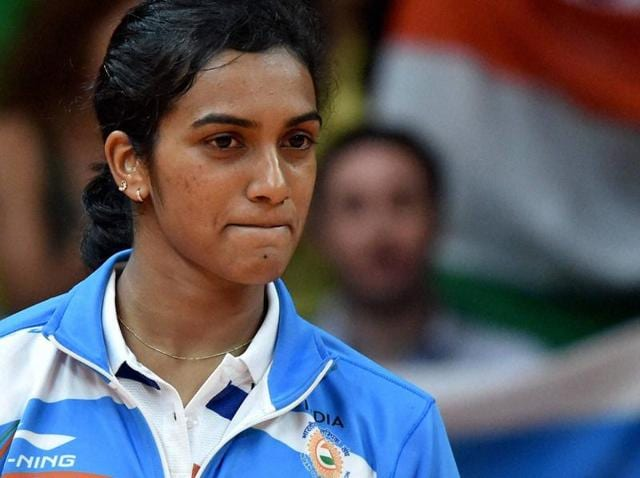 PV Sindhu poses with the national flag during the victory ceremony.