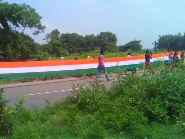 More than 5,000 schoolchildren, volunteers and others formed a human chain holding a 7,100-metre Tricolour in Bihar's Purnia on Saturday.(HT Photo)