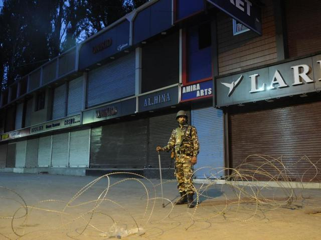 Paramilitary soldier stands guard during curfew in Srinagar, Jammu and Kashmir, August 17 2016. Mobile phone services in Kashmir valley were partially restored on August 20, 2016 though restrictions and curfew continued in many areas.