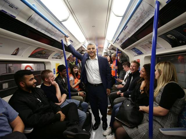 London Mayor Sadiq Khan (left) travels down an escalator with the public at Brixton underground station during the launch of the Night Tube service on Saturday.