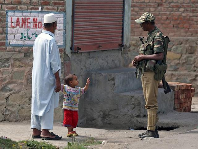 A boy gestures at a member of the security forces in Srinagar as the city remains under curfew following weeks of violence in Kashmir.