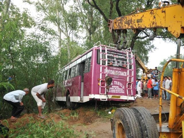 One of the buses being pulled out of the trees with a crane near the village Billi Chaharmi on the Jalandhar-Moga highway on Saturday.
